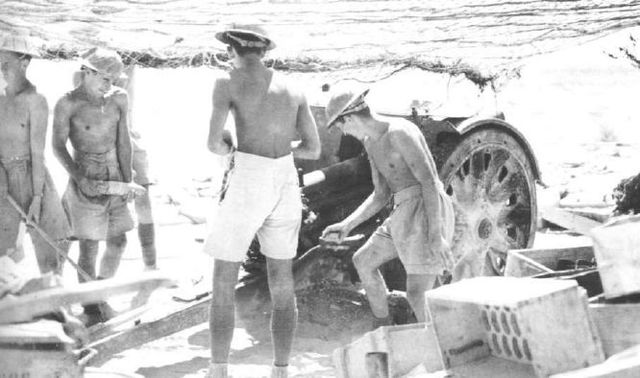 Artilleros australianos manejando una pieza de artillería capturada a los italianos en Tobruk
